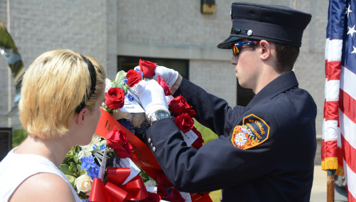 A student who is a member of the Bethpage Volunteer Fire Department places a rose on a wreath in memory of one of the 27 members of the Hofstra Community killed on 9-11.