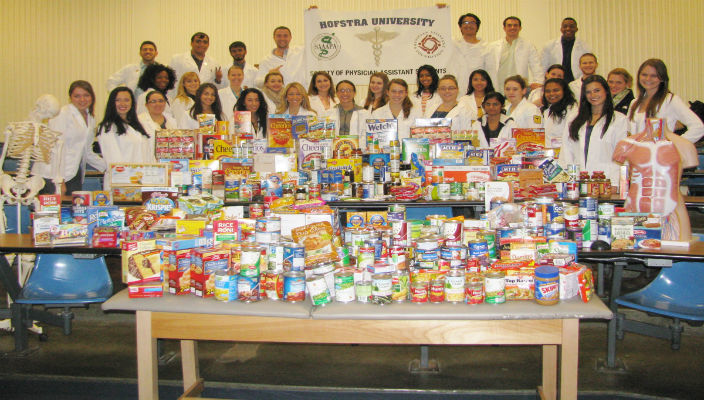 The Physician Assistant Studies Program class of 2015 with the 930 items of food from their food drive on campus.