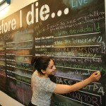 """Jasmina Ehab'15 adds her thoughts to the  """"Before I Die..."""" wall in the Hofstra Dome."""