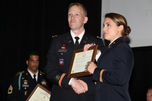 2LT Jessica Dufault receives a certificate from LTC Cederman indicating she is a Distinguished Military Graduate.