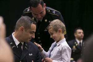 Cadet Siarhei Ulitenok has his 2LT rank fastened to his uniform by his son during the ceremony.