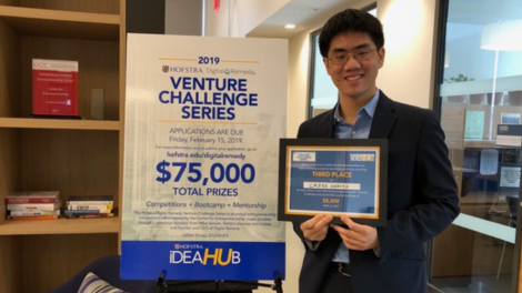 Student Michael Lai standing with his award from the Hofstra-Digital Remedy Venture Challenge