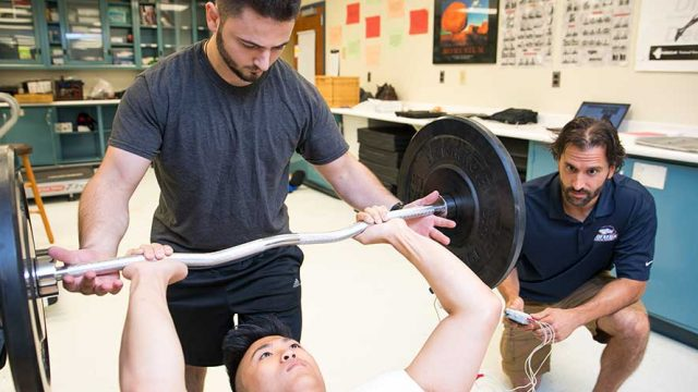 Exercise science professor and students working through exercise routine and evaluation.