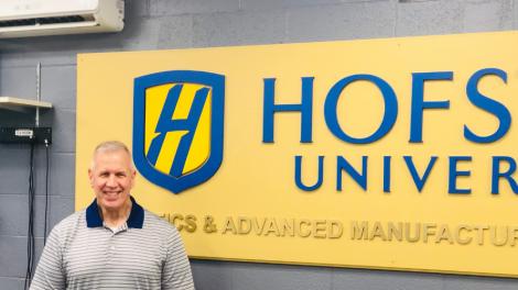 Professor Kevin Craig next to a Hofstra University Sign.