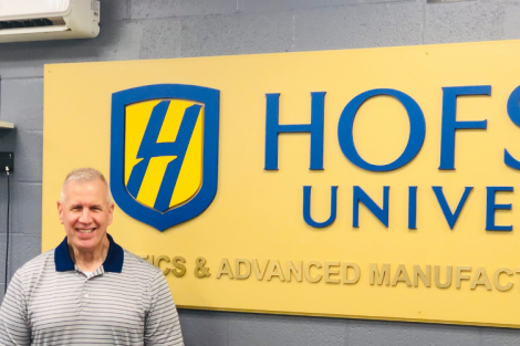 Professor Kevin Craig next to a Hofstra University Sign.