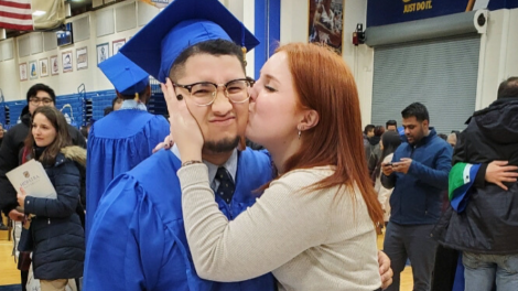 Couple kissing at commencement