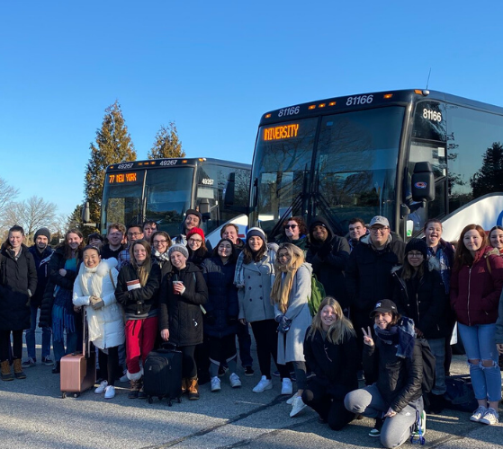 Group of students in front of two coach buses.